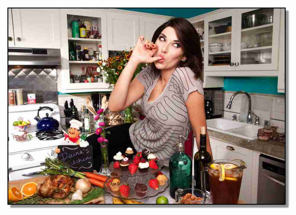 woman licking her finger in front of food on counter