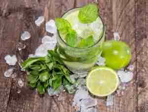 Glass with Mojito and crushed ice on wooden background - Miami outdoor kitchen
